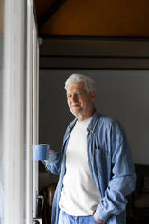 Confident senior man holding coffee mug while standing by window at home - AFVF06553