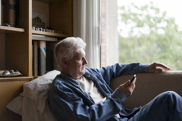 Senior man using smart phone while relaxing on sofa at home - AFVF06559