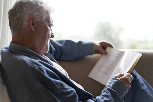 Senior man reading book while relaxing on sofa at home - AFVF06562