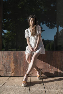 Beautiful young woman in mini dress sitting on wooden plank during sunny day - MTBF00426