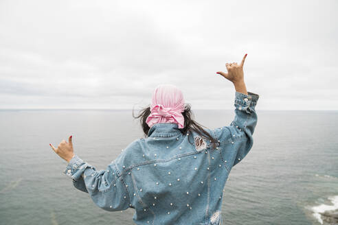Female cancer survivor gesturing while looking at sea against cloudy sky - MTBF00432