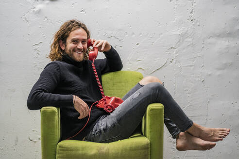 Smiling man talking over telephone while relaxing on armchair against wall - DLTSF00721