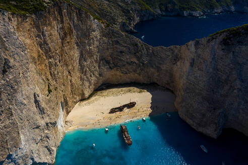 Aerial view of an abandoned boat on the shore of Navagio beach surrounded by turquoise water, Greece - AAEF08860
