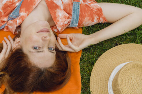 Beautiful young woman relaxing on grass at back yard - AFVF06582