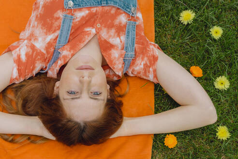 Relaxed young woman lying with hands behind head on picnic blanket by flowers at back yard - AFVF06585