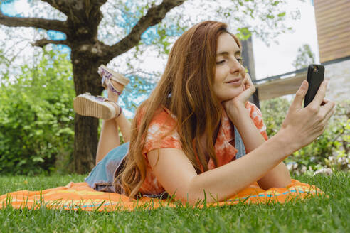 Smiling beautiful woman using smart phone while lying at back yard - AFVF06588