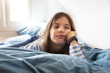 Portrait of bored little girl lying on bed - LVF08925