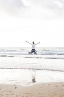 Carefree young man with arms outstretched jumping at beach against sky - FVSF00379