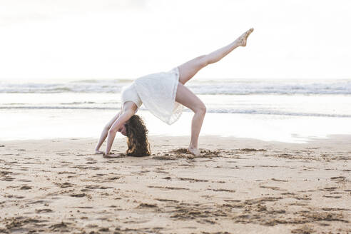 Young woman wearing white dress dancing on sand at beach against clear sky - FVSF00382