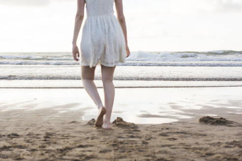 Young woman wearing white dress walking barefoot on sand at beach against clear sky - FVSF00385
