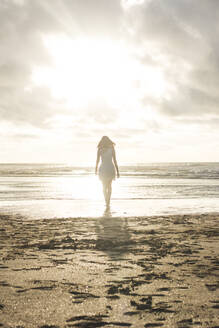 Young woman walking at beach against cloudy sky during sunset - FVSF00388