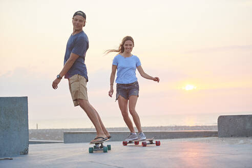 A young couple, man and woman skateboarding by the beach at sunset. - ISF24176