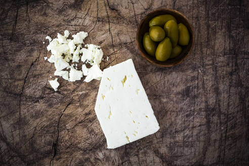 Feta cheese and bowl of fresh olives on wooden surface - GIOF08351