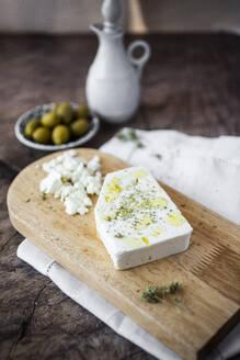 Feta cheese on cutting board - GIOF08354