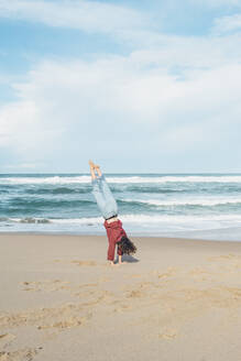 Young woman doing handstand at Ursa beach against sky, Portugal - FVSF00434