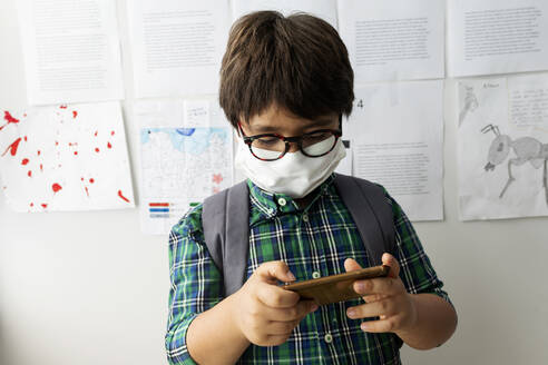 Boy wearing mask using mobile phone while standing against wall in school - VABF03007
