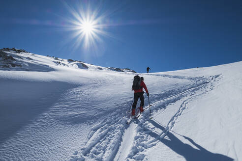 Senior man skiing on snow covered Dachstein mountain against sky during sunny day, Austria - HAMF00626