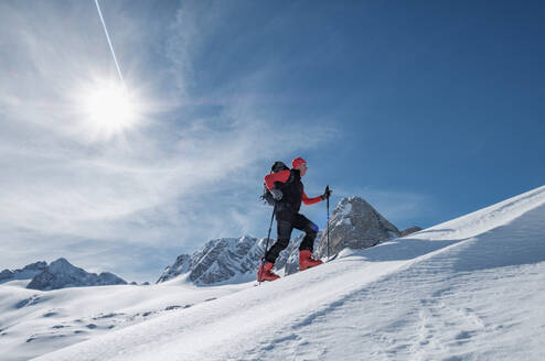 Senior man skiing on snow covered Dachstein mountain against sky during sunny day, Austria - HAMF00629
