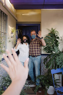 Couple wearing masks waving hands to neighbor while standing at entrance of house - AGGF00076
