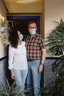 Couple wearing masks standing against house entrance - AGGF00079