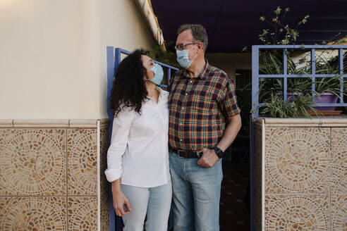 Couple wearing masks looking at each other while standing outdoors - AGGF00082