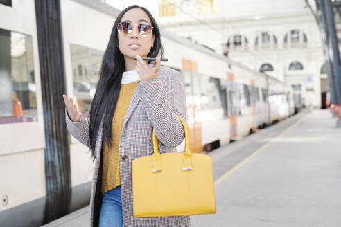 Woman wearing sunglasses talking over smart phone while standing at railroad station - JCZF00127