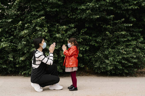 Mother and daughter wearing masks while playing clapping game on street - EGAF00123