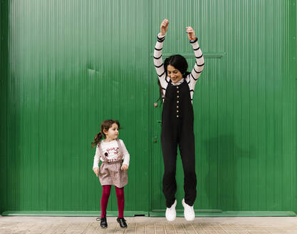 Playful mother and daughter jumping against green corrugated wall - EGAF00132