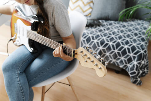 Woman playing electric guitar while sitting on chair at home - JMHMF00056