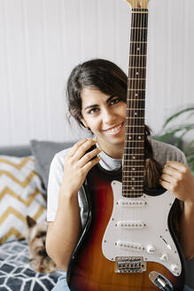 Happy woman holding electric guitar while sitting on sofa at home - JMHMF00059