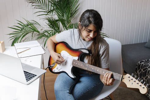 Young woman playing electric guitar while sitting on chair at home - JMHMF00062