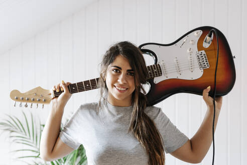Happy young woman carrying electric guitar on shoulder at home - JMHMF00071