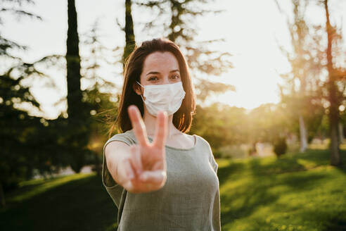 Portrait of woman wearing protective mask in nature showing victory sign - EBBF00181