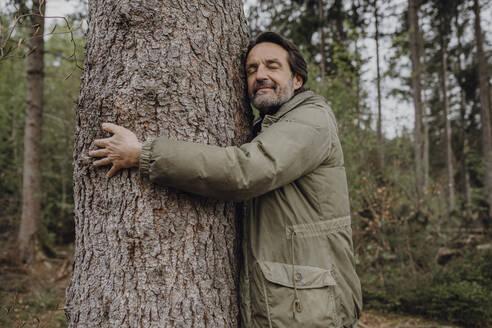 Mature hiker hugging tree trunk - JLOF00440