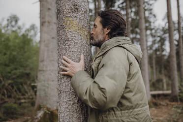 Mature hiker kissing tree trunk - JLOF00449