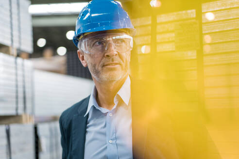 Portrait of mature businessman wearing hard hat and safety goggles in a factory - MOEF02941
