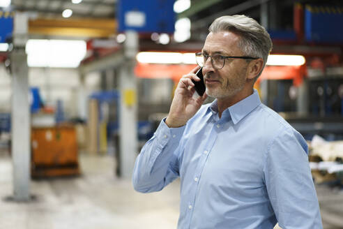 Mature businessman on the phone in a factory - MOEF03004