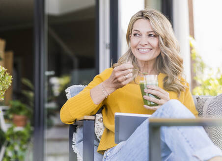 Portrait of smiling mature woman sitting on terrace with digital tablet enjoying green smoothie - UUF20534