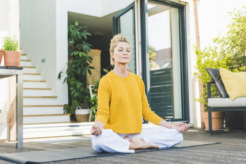 Portrait of mature woman meditating on terrace - UUF20573
