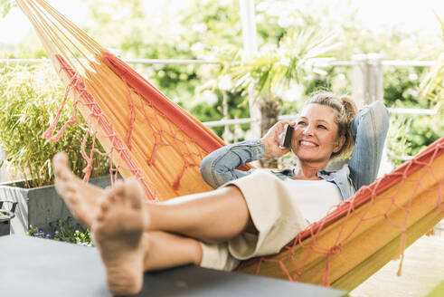 Portrait of happy mature woman on the phone relaxing in hammock on terrace - UUF20603