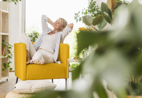 Portrait of smiling mature woman relaxing in armchair at home - UUF20612