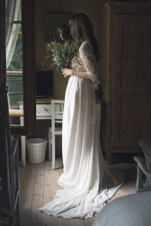 Young woman in elegant wedding dress holding bouquet in front of mirror - ALBF01258