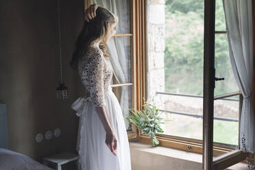 Young woman in elegant wedding dress holding bouquet looking out of the window - ALBF01264