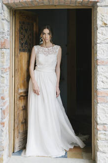 Young woman in wedding dress walking through door - ALBF01267