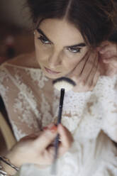 Hands applying cosmetics on face of bride - ALBF01276