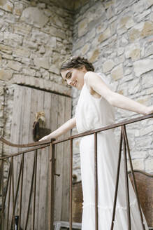 Young smiling woman in elegant wedding dress at railing - ALBF01279