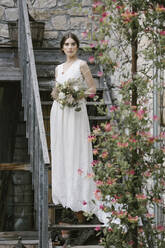Young woman in elegant wedding dress with bouquet standing on stairs - ALBF01282