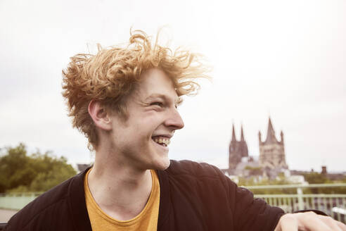 Portrait of laughing young man with blowing hair, Cologne, Germany - FMKF06225