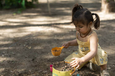 Little girl playing with soil in a park - VABF03010