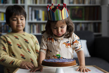 Portrait of little girl blowing out candle on her birthday cake at home - VABF03022